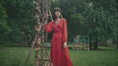 Woman in red holding a swing in an abandoned park
