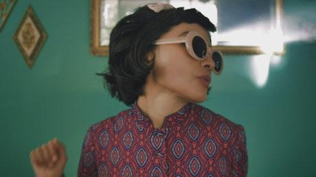 Woman in sunglasses dancing at home