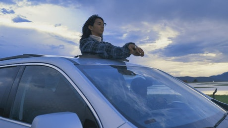 Woman in sunroof on a road trip through nature