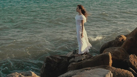 Woman in white dress looking out to sea