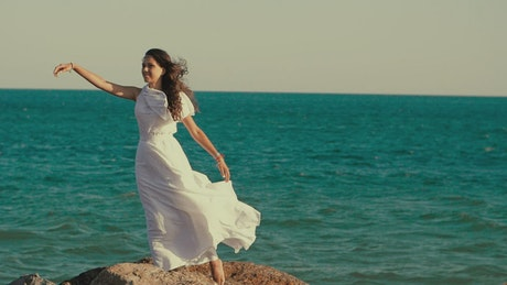 Woman in white dress posing by the sea