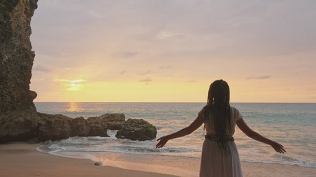 Woman in white dress raises her hands on the beach