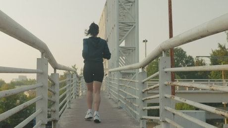 Woman jogging across a narrow footbridge