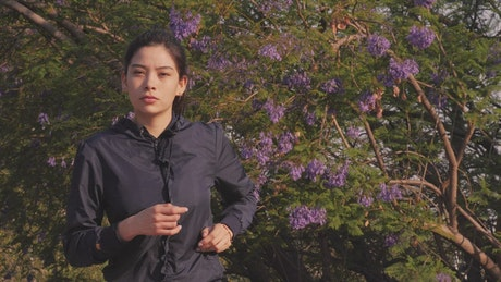 Woman jogging head-on outdoors