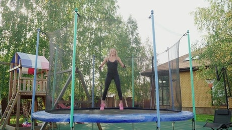 Woman jumping on a small trampoline