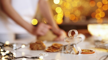 Woman kneading cookie dough with bokeh lights