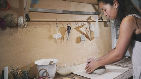 Woman kneads clay in the workshop