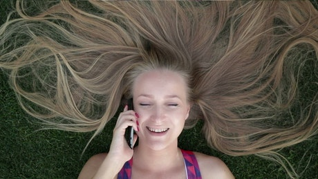 Woman laying down and talking on the phone