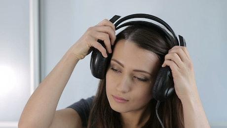 Woman listening to music on her headphones, portrait