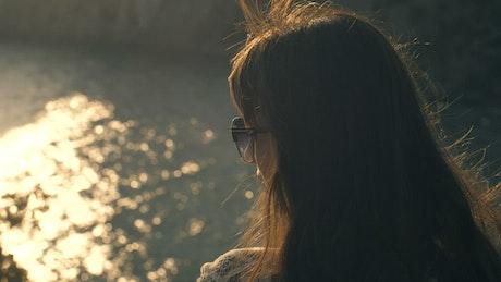Woman looking at a lake reflecting the sun