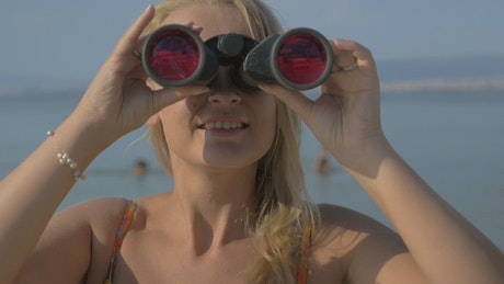 Woman looking through binoculars at the beach