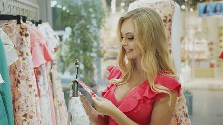 Woman looks at a dress in a store