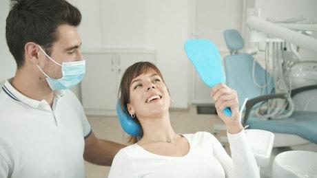 Woman looks at teeth in dentist office mirror