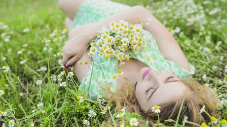 Woman lying in the grass with a bouquet of flowers
