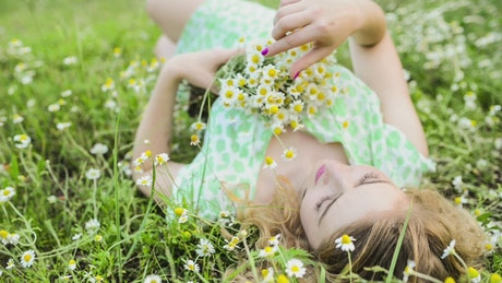 Woman lying on the meadow with a bouquet of small flowers