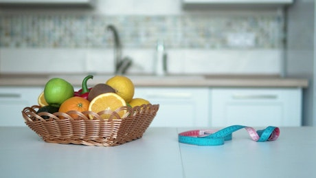 Woman measures weight loss progress in kitchen