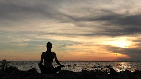 Woman meditating at the coast