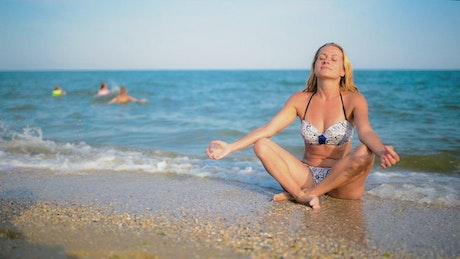 Woman meditating at the seashore