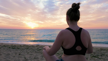 Woman meditating by the ocean