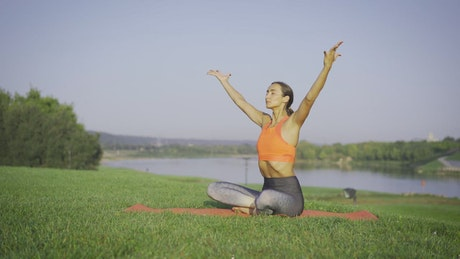 Woman meditating on the grass near the river