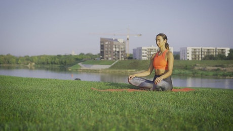 Woman meditating on the park by the river