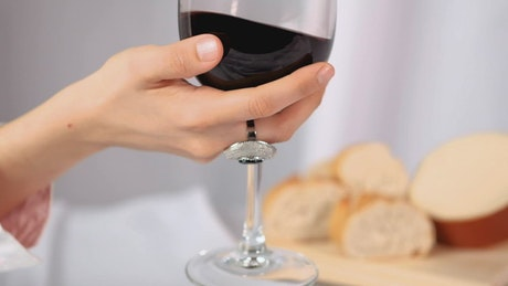 Woman mixing red wine in a glass goblet