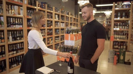 Woman offers wine selection to customer