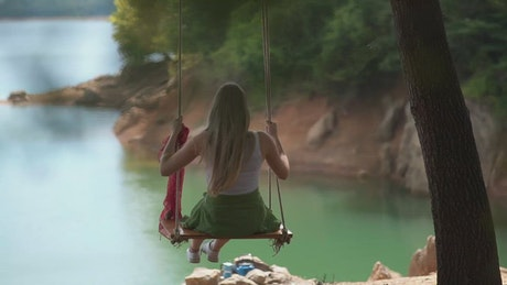 Woman on a swing by the lake