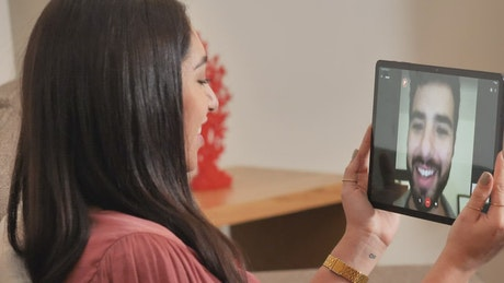 Woman on a video call with a man by tablet
