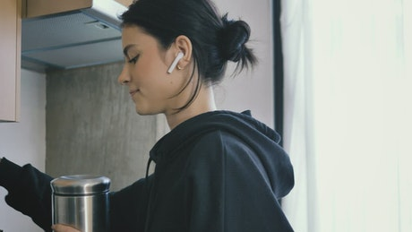 Woman on call with earphones while preparing coffee