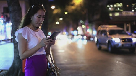 Woman on the street sending messages at night