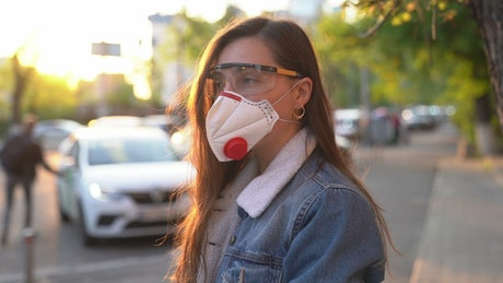 Woman on the street with a face mask and protection glasses