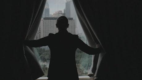 Woman opening dark curtains