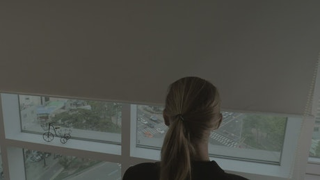 Woman opening office blinds