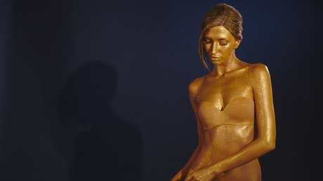 Woman painted completely in gold posing
