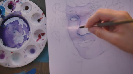 Woman painting a face with watercolors