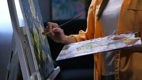 Woman painting a picture with brush, close up