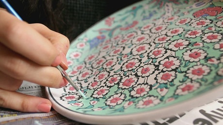 Woman painting flowers hand on a large plate