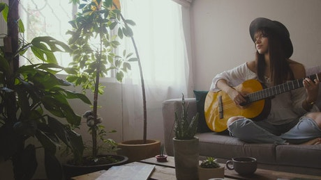Woman playing an acoustic guitar in her living room