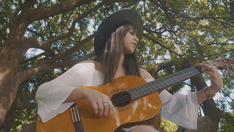 Woman playing an acoustic guitar outside