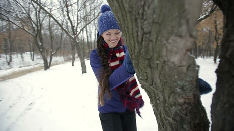 Woman playing around a tree during winter