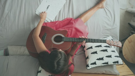 Woman playing the acoustic guitar on the bed