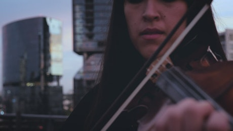 Woman playing violin in the city