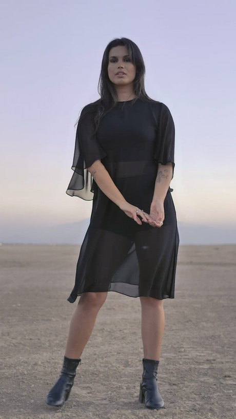 Woman posing for the camera in the middle of a desert