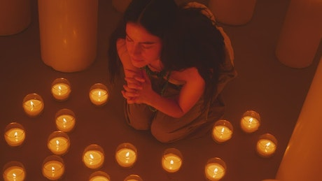 Woman praying, sitting on the floor among many candles