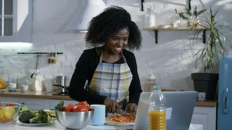 Woman prepares food following a tutorial
