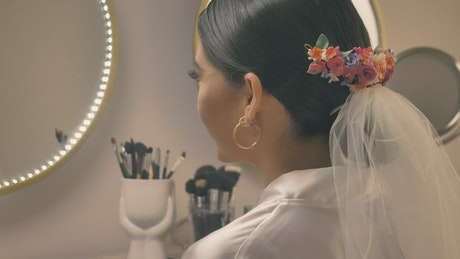 Woman preparing for her wedding in front of the mirror