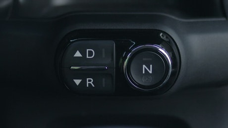 Woman pressing the reverse button on a dashboard