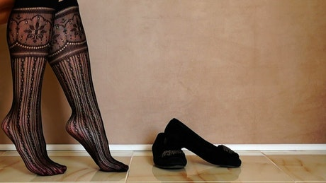 Woman putting on black shoes