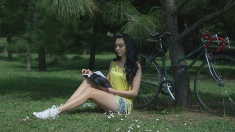 Woman reading a magazine in the park